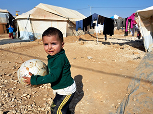 A boy hangs on to a damaged ball in the Zaatari Refugee Camp, located near Mafraq, Jordan. Opened in July, 2012, the camp holds upwards of 20,000 refugees from the civil war inside Syria. International Orthodox Christian Charities and other members of the